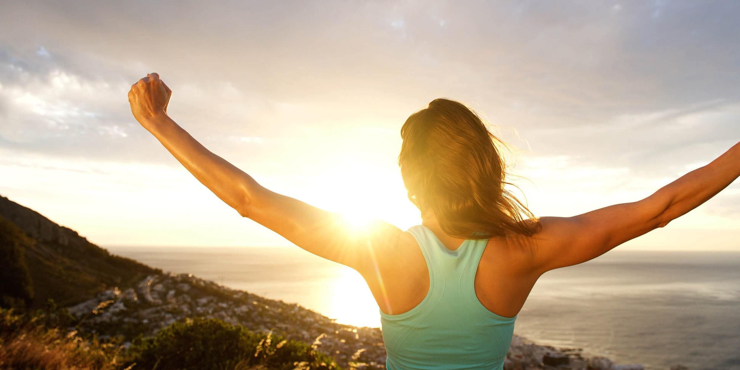 Woman from behind stretching out arms by sunrise